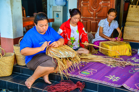 Phayao, Thailand - February 15, 2014: Women weaving wicker handbag made from papyrus in Phayao, Thailand