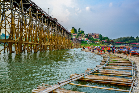 Kanchanaburi, Thailand - April 12, 2014: Long wooden Mon bridge destroyed and damaged by stream of strong flood with temporary wooden bridge in Sangkhlaburi of Kanchanaburi, Thailand