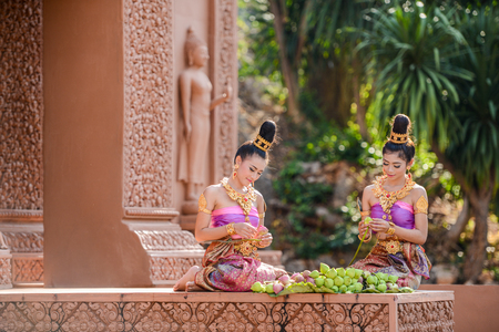 Kanchanaburi, Thailand - December 14, 2014: Women with traditional dresses folding lotus petal for being used to worship Buddha image in Buddhist church in Kanchanaburi, Thailand