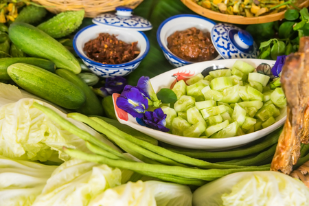 selectively: Various Thai vegetables, spices  and chili sauce in basket, ready for cooking, selectively focus Stock Photo