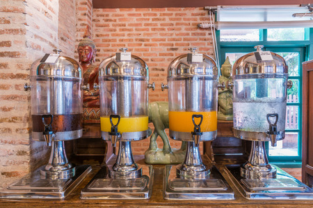 Juice of orange, apple, pineapple and water in glass dispenser to provide to customers in restaurant Stock Photo