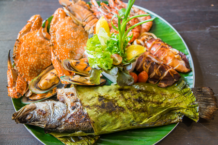 Dish of mixed grilled seafood including, fish, crab, mussel, shrimp, squid on wooden table