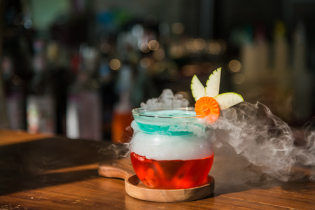 Cocktail drink in favor with smoke on wooden plate on wooden cocktail bar