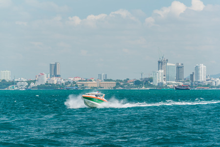 Tourist speed boat running on sea in Pattaya bay with background of Pattaya city in a mist