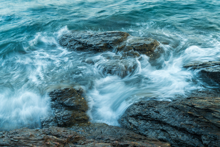 Wave in sea hitting rock on coast in the evening in national park Stock Photo