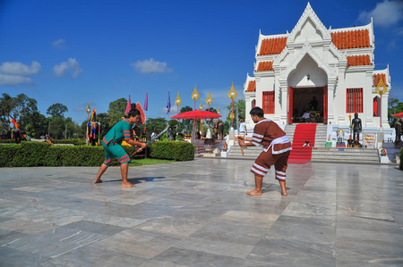 Phitsanulok, Thailand - April 8, 2011: Two men in traditional dress holidng sword demonstrating Thai traditional fencing outdoor to tourists in front of King Naresuan shrine in Phitsanulok, Thailand Redactioneel