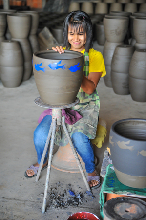 Nakhon Sawan, Thailand - December 5, 2011: Woman artist screening graphics image to formed pottery in the workshop in Sukhothai, Thailand Éditoriale