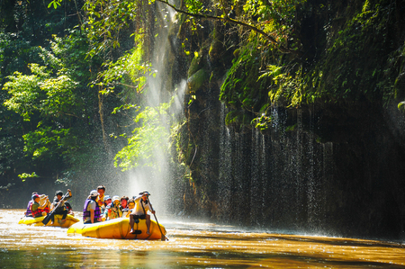 Tak, Thailand - November 9, 2011: Group of tourists rafting in rubber boats on the river through waterfalls in national park in Tak, Thailand