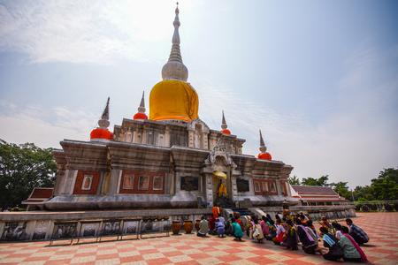Maha Sarakham, Thailand - October, 26, 2013: Buddhists and monks worshiping Buddha Image in front of Nadun Pagoda in Maha Sarakham, Thailand