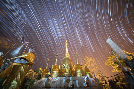 Startrails over the beautiful group of golden pagodas in Buddhist temple in Kanchanaburi, Thailand