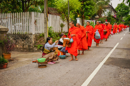 Luangprabang, Laos - December 8, 2015: Laos people offering food and things to group of Buddhist monks in morning on rural street in Luangprabang, Laos Editorial