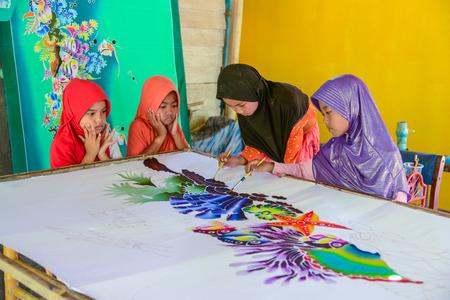 Krabi, Thailand - May 2, 2015: Cute Muslim girls wearing black and purple hijab painting pattern on Batik fabric in her home in Krabi, Thailand