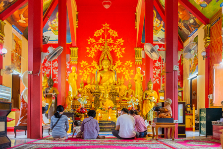 Ayutthaya, Thailand - July 08, 2018: Buddhist people worshiping beautiful golden Buddha Image in Buddhist church in Ayutthaya, Thailand