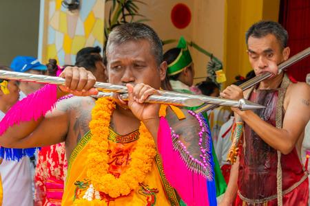 Phang Nga, Thailand - October 14, 2018: Man demonstrating sharp steel run through the mouth in vegetarian festival parade in Phang Nga, Thailand