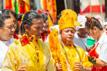 Phang Nga, Thailand - October 14, 2018: Woman demonstrating sharp steel run through the mouth in vegetarian festival parade in Phang Nga, Thailand Editorial