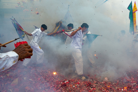 Phang Nga, Thailand - October 14, 2018: Group of men in white dress holding palanquin with Chinese god statue inside  marching on street while people fire firecracker to worship the god in vegetarian festival parade in Phang Nga, Thailand Editorial