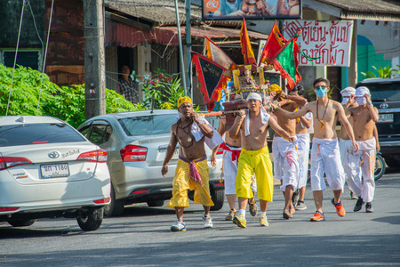 Phang Nga, Thailand - October 15, 2018: Group of men in white dress holding palanquin with Chinese god statue inside  marching on street in vegetarian festival parade in Phang Nga, Thailand Editorial