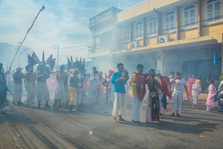 Phang Nga, Thailand - October 15, 2018: Group of men in white dress holding palanquin with Chinese god statue inside  marching on street while people fire firecracker to worship the god in vegetarian festival parade in Phang Nga, Thailand Editorial