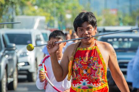 Phang Nga, Thailand - October 15, 2018: Man demonstrating sharp steel run through the mouth in vegetarian festival parade in Phang Nga, Thailand