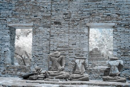 Ruined Buddha image in ruined ancient Buddhist temple and pagoda in Ayutthaya historical park, Thailand in infrared photography Stock Photo