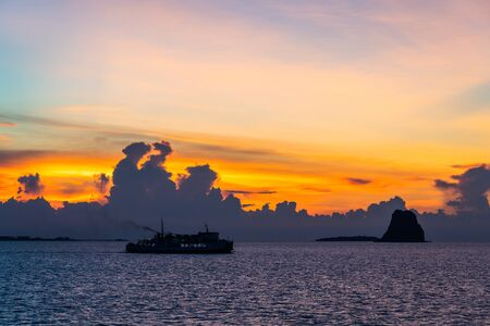 Silhouette unidentified ferry ship running sea during beautiful sunset