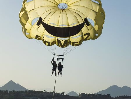 SHARM EL SHEIKH, EGYPT - June 19, 2015: Two people are flying on a yellow parachute over the sea Editorial