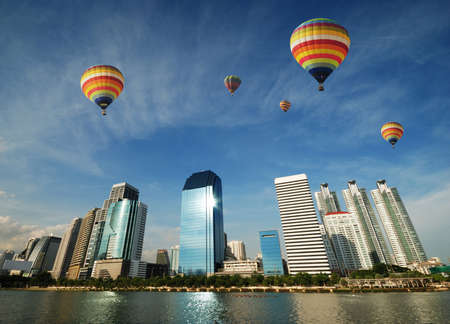 Colorful balloons floating over Bangkok skyscraper photo
