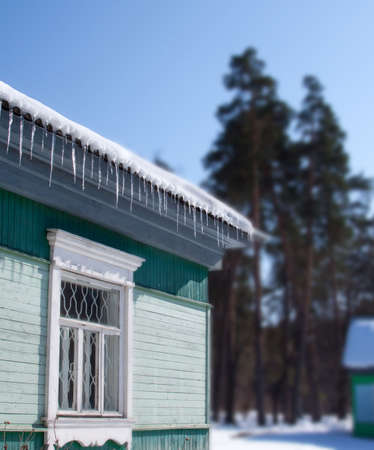 Spring view in countryside - roof with icicles against a blue sky