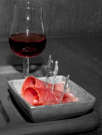 A glass of french red wine and italian parma on the tray