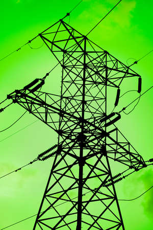 High voltage electricity pylon silouette against green background