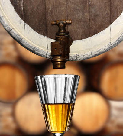 glass underneath a wine or beer wooden keg against wooden barrel background