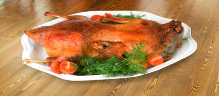 Roasted duck on a plate on wooden surface Stock Photo