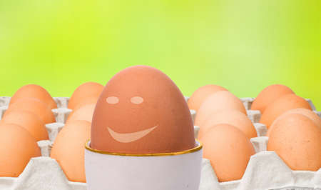 Leadership concept represented through eggs, one happy egg is out of crowd leading others Stock Photo