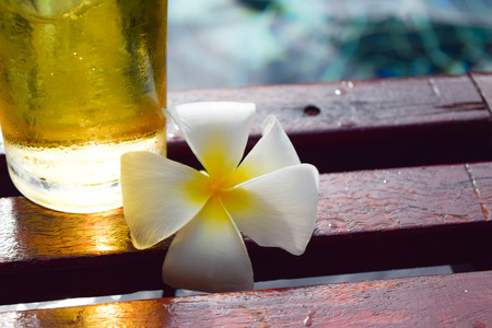 swiming: a glass of beer with plumeria flower on wooden chair in swiming pool
