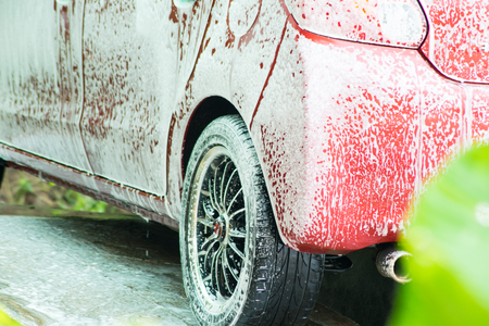 a red car is washing in foam Stock Photo