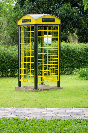 antique booth: Yellow phone booth on green grass
