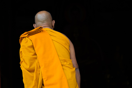 closeup back of thai monk on black background