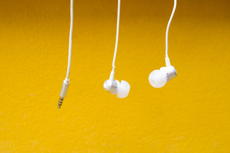 phone cord: white headphone on yellow background Stock Photo