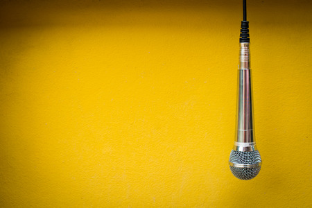 close up microphone on yellow background