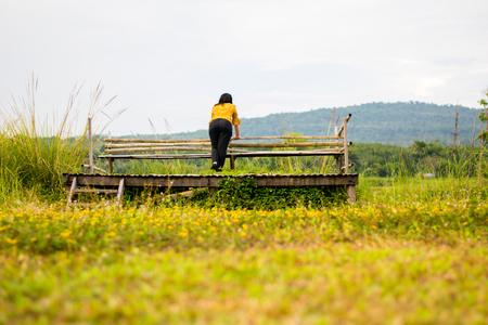 pretty girl on wooden chair in yellow flower field