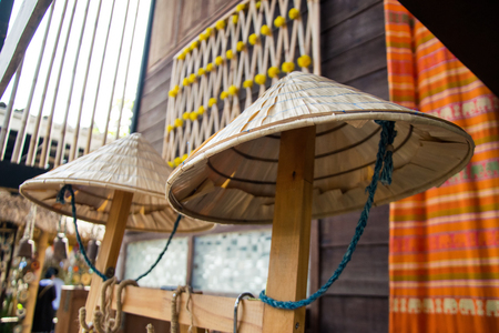 Palm leaf hat on wooden house background