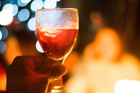 Hand holding glass of champagne for celebration in dinner party