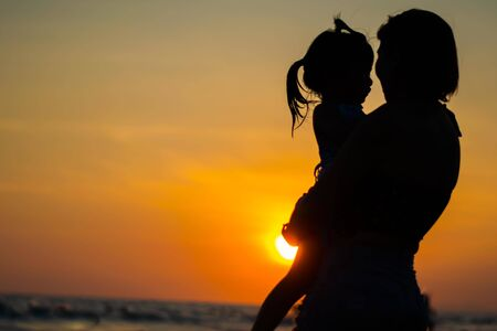 silhouette of lovely mother and her baby on sunset beach