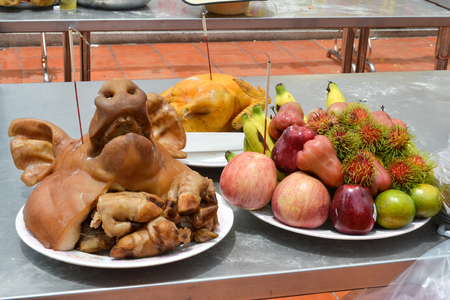 Pig head, boiled chicken and  fruit for oblation vow