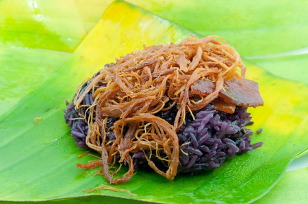 Black sticky rice with fried pork Covered with banana leaf Thai street food  photo