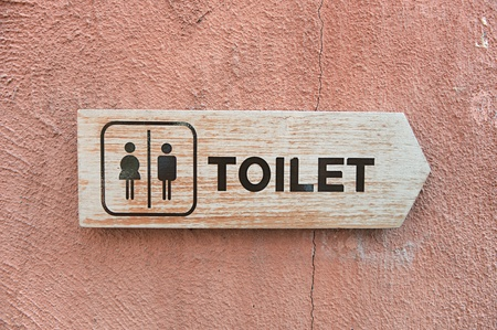 defecate: toilet plate sign on wall  Stock Photo