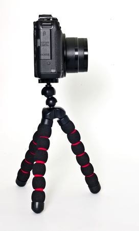 compact camera: Black compact camera that is placed on a small stand on a white background. Stock Photo