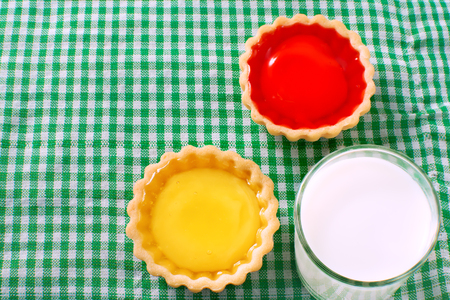 Tarts jam and milk on a green tablecloth.