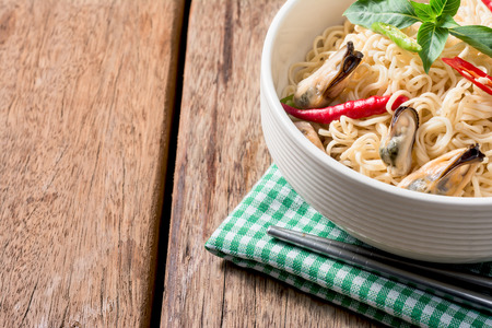 cooked instant noodle: Instant noodles with mussels on a wood table cloth and place mat green.