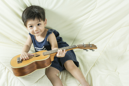 thai musical instrument: Baby Boy playing ukulele On the couch happily. Stock Photo